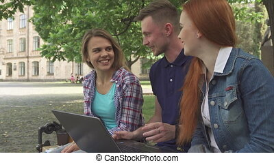 Students work on laptop on campus
