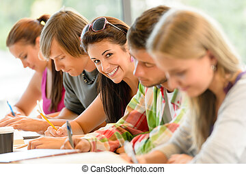 Students writing at high-school exam teens study campus...