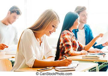studerend , met, pleasure., vrolijke , jonge vrouw , schrijvende , in, opmerking blok, en, het glimlachen, terwijl, zittende , op, haar, bureau, in, de, klaslokaal