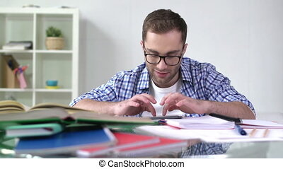 Studies Made Easy - Smiley guy doing homework using portable...