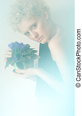 Studio, blurring - young sexy romantic girl in blur with flowers in their hands.