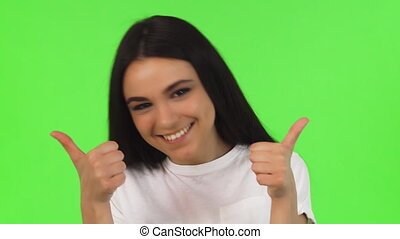 Studio close up of a happy girl showing thumbs up on green background