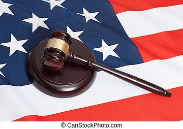 Studio close up shot of a judge gavel over flag of United...
