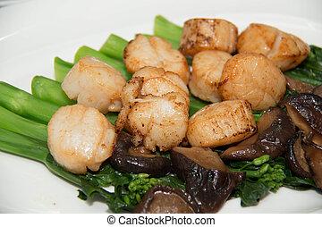 Studio closeup of seared scallops, garnished with vegetables