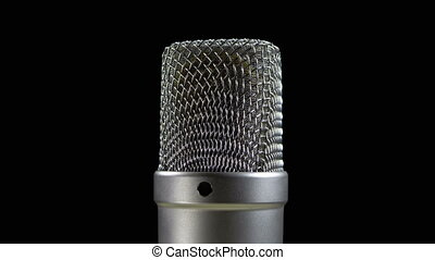 Studio Condenser Microphone Rotates on a Black Background....