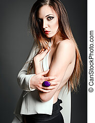 Studio fashion shot: a sexy beautiful girl in white jacket against gray background