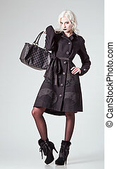 Studio fashion shot: beautiful girl in black coat and boots, with bag in hand