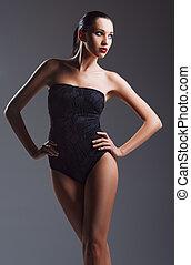 Studio fashion shot: beautiful young woman wearing black body