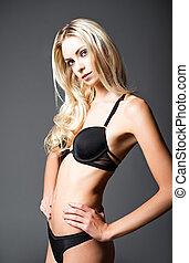 Studio fashion shot of beautiful young woman in underwear