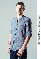Studio fashion shot: portrait of handsome young man wearing jeans
