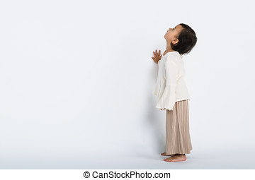 Studio full body portrait of a young girl gazing into the sky against a wall