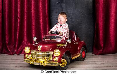 Studio image of baby posing in big toy car at studio