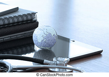 Studio macro of a stethoscope and texture globe with digital tab