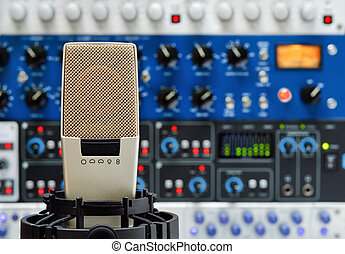 Professional studio microphone and a rack of audio devices, with shallow focus