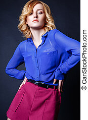 Studio photo of young curly blonde woman on black background.
