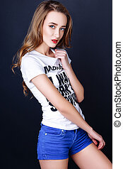 Studio photo of young woman on black background.
