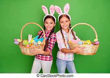 Studio photo portrait of two beautiful pretty charming sweet kind lovely dream dreamy in casual plaid shirt jeans denim pants showing full filled wooden baskets isolated bright vibrant background