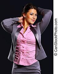 Studio portrait of a businesswoman in suit, against dark background