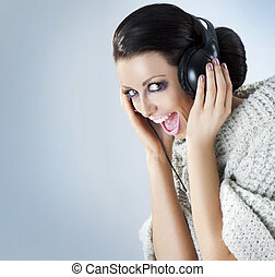 Studio portrait of a girl in headphones listening music