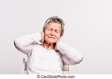 Studio portrait of a senior woman in pain on a white background.