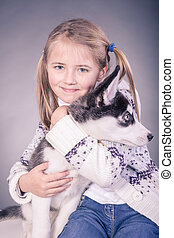 girl with a husky puppy