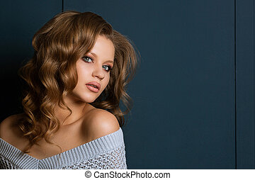 Studio portrait of attractive blonde model with perfect skin and makeup, posing in the shadows. Empty space