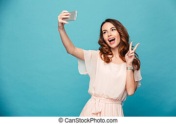 Studio portrait of beautiful woman in dress smiling with white teeth and taking selfie, photographing herself, isolated over blue background