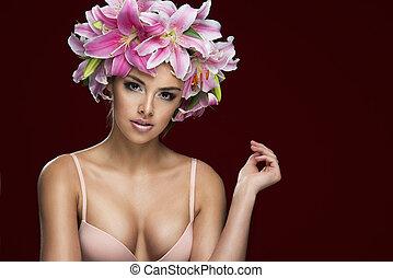 studio portrait of beautiful woman wearing flowers in her hair