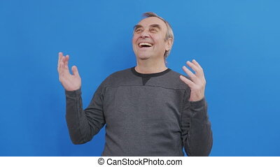 Studio portrait of confident smiling elderly man laughing against blue background