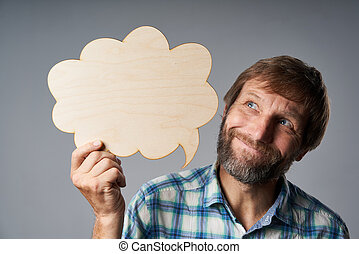 Studio portrait of dreaming mature man holding speech bubble