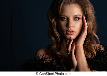 Studio portrait of fashionable blonde girl with perfect skin and makeup, posing in the shadows. Empty space