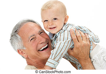 Studio Portrait Of Grandfather Holding Grandson