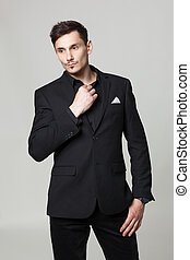 Studio portrait of handsome elegant young man in black  clothes posing.