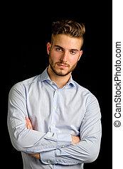 Studio portrait of handsome young businessman looking in camera