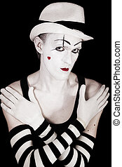 Studio portrait of mime in white hat and striped gloves