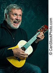 Studio portrait of senior man with guitar.