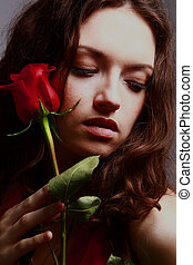Studio portrait of sensual beautiful woman with rose.