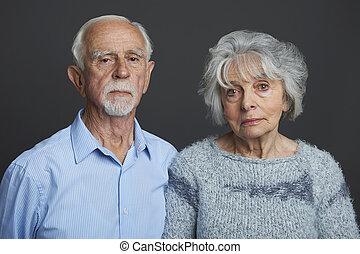 Studio Portrait Of Serious Senior Couple