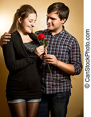 portrait of smiling man giving red rose to cute girlfriend