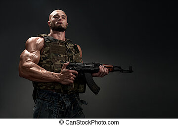 portrait of soldier with a gun on black background