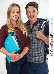Studio Portrait Of Teenage Student Couple On White Background