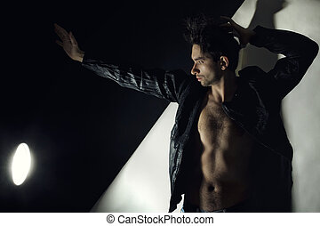 Studio portrait of young man wearing a jacket with dark hair naked breast