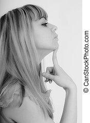 Studio portrait of young pensive woman in profile