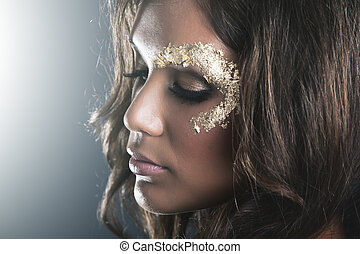 Studio portrait with dark skin and golden makeup