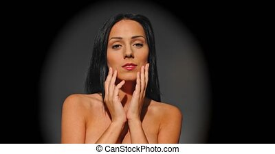Beautiful nude woman touching and massaging her face. Front view on dark background