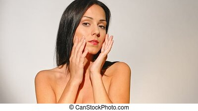Studio shoot of beautiful nude woman touching and massaging her face. Front view on grey background