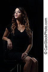 Studio shoot of beauty woman posing on the chair