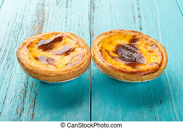 studio shoot of portuguese egg tarts at side view on a wood background