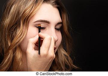 Studio shot of a girl putting make up on