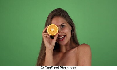 Studio shot of a gorgeous happy woman smiling holding half of an orange